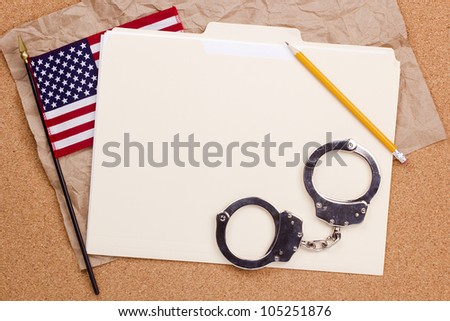 Directly above photograph of handcuffs, folder, and the American flag. - stock photo