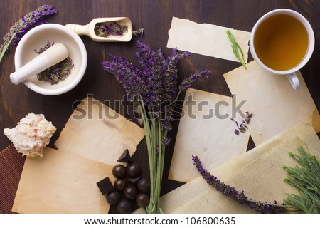 Directly above photograph of lavender flowers, papers, and decorative objects to portray the topic of alternative medicine. Add your text to the papers.