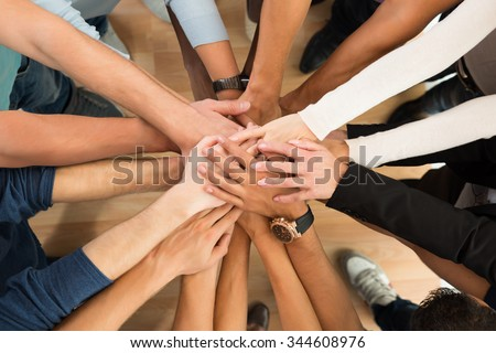 Directly above shot of creative business people piling hands over white background - stock photo