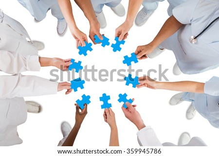 Directly above shot of medical team holding blue jigsaw pieces in huddle against white background - stock photo