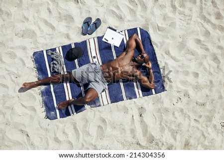 Directly above shot of  muscular young african guy sunbathing on beach. Man wearing sunglasses listening to music on while lying on a beach mat outdoors. - stock photo