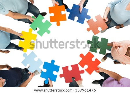Directly above shot of team holding colorful jigsaw pieces in huddle against white background - stock photo