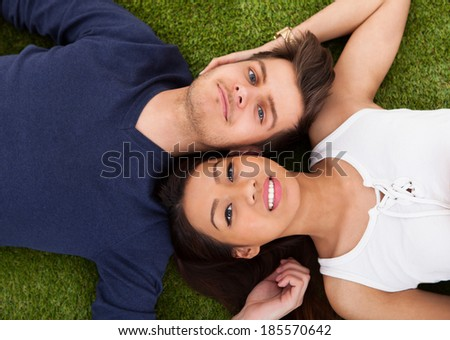Directly above shot of young couple lying on grass in park