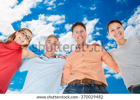 Directly below portrait of happy friends forming huddle against sky