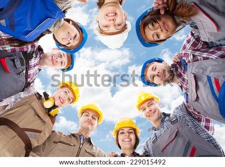 Directly below portrait of multiethnic architects standing in huddle against sky - stock photo