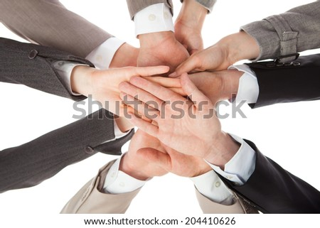 Directly below shot of business people stacking hands against white background