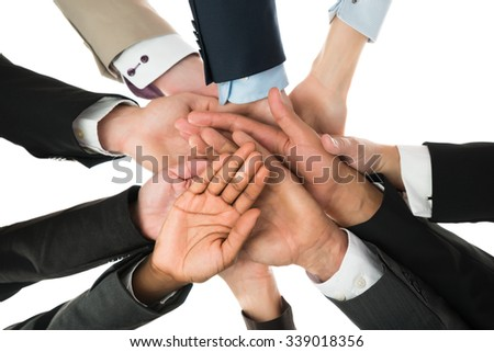 Directly below shot of business team stacking hands against white background