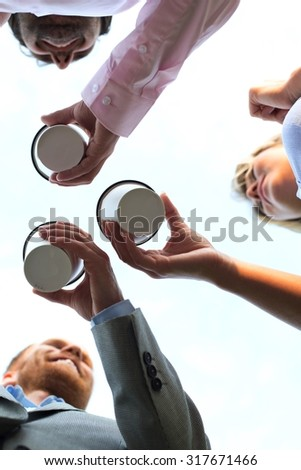 Directly below shot of businesspeople holding disposable cups against clear sky - stock photo