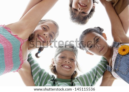Directly below shot of children forming huddle against clear sky - stock photo