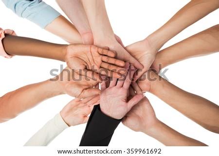 Directly below shot of creative business team piling hands against white background