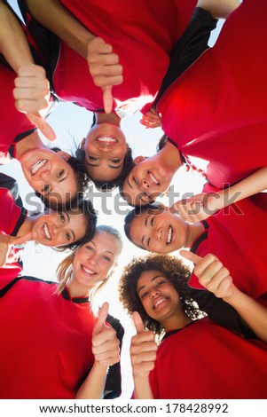 Directly below shot of female soccer team gesturing thumbs up while forming huddle against clear sky - stock photo