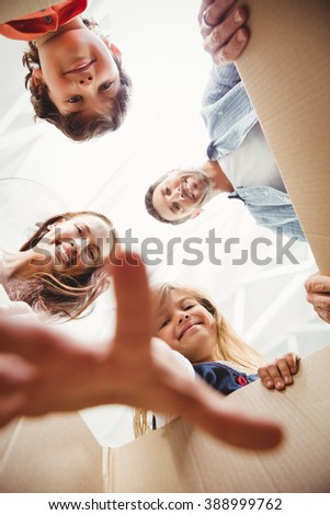 Directly below shot of happy family with cardboard boxes - stock photo