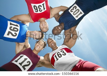 Directly below shot of multiethnic track and field athletes forming huddle against sky - stock photo