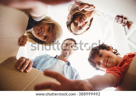 Directly below shot of smiling family with cardboard boxes - stock photo