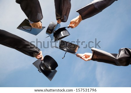 Directly below shot of students raising mortar boards against sky on graduation day - stock photo