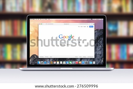 Directly front view of Apple 15 inch MacBook Pro Retina with an open tab in Safari which shows Google search web page. Blurred bookshelves on the background. Varna, Bulgaria - November 03, 2013. - stock photo