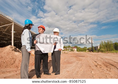 Director and engineers on construction site of shopping center
