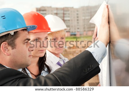 Director and engineers on construction site of shopping center - stock photo