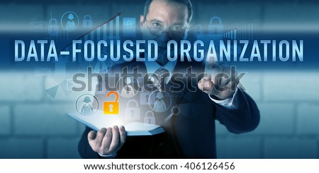 Director pressing DATA-FOCUSED ORGANIZATION on a virtual touch screen interface. Business strategy metaphor and information technology concept for enterprise decisions and operations driven by data. - stock photo