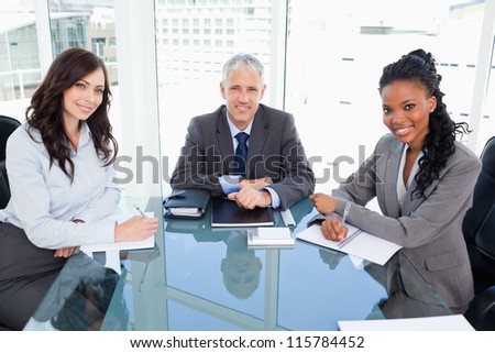 Director smiling and sitting at the desk in front of the window between two co-workers - stock photo