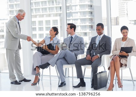 Director welcoming a businesswoman in a waiting room - stock photo