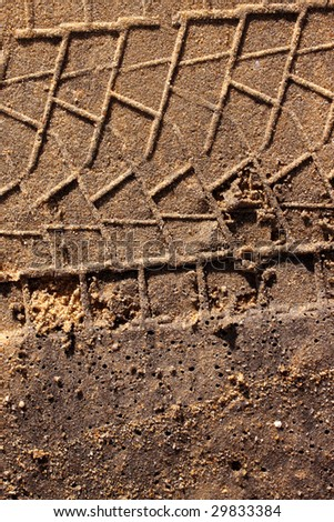 Dirt background with vehicle pattern track - stock photo