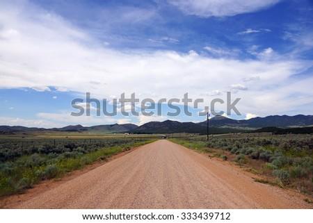 Dirt Desert Road and Blue cloudy Sky in Utah. - stock photo