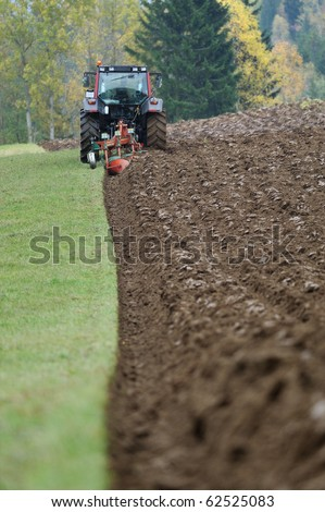 Dirt land and tractor - stock photo