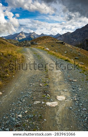 Dirt mountain road crossing alpine slopes and meadows with dramatic stormy sky and panoramic view. Piedmont, Italian Alps. - stock photo