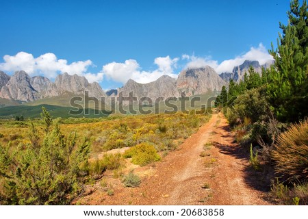 Dirt red road towards majestic mountains. Shot in Hottentots-Holland Mountains nature reserve, near Somerset West/Cape Town, Western Cape, South Africa. - stock photo