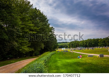 Dirt road and cemetery in rural York County, Pennsylvania. - stock photo
