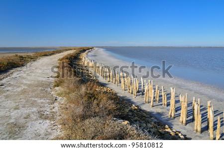dirt road in an abandoned salt evaporation pond, in Camargue natural park, France - stock photo