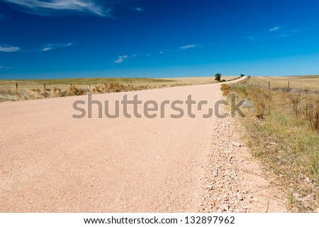 Dirt road in country Australia stretches into the distance under a blue sky - stock photo