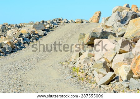 Dirt road in gravel pit with small slope up. - stock photo