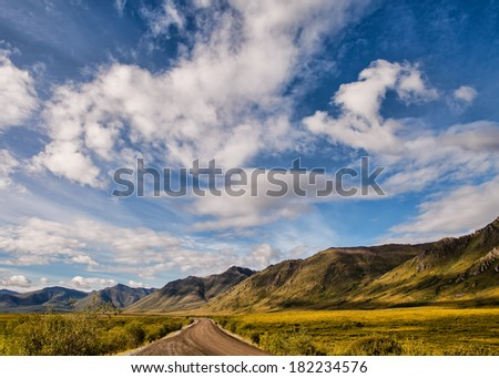 Dirt road in Yukon Territory in summer with blue sky and clouds. - stock photo