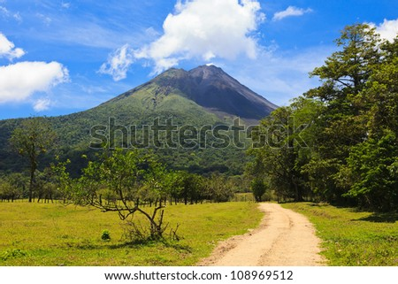 Dirt road leading to the Arenal Volcano in Costa Rica. - stock photo