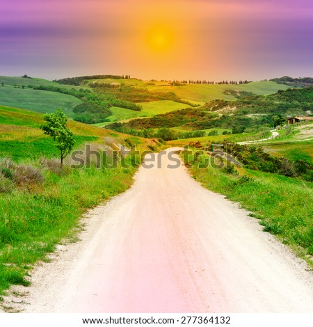 Dirt Road Leading to the Farmhouse in Tuscany at Sunset - stock photo