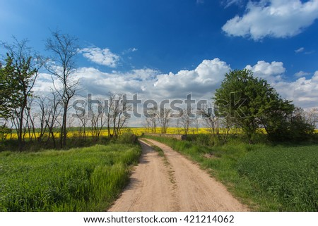 Dirt road leads through the fields on the bridge. Sunny spring day. Czech Republic Europe - stock photo
