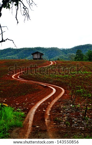 Dirt road passing the hut and mountain range. thailand - stock photo