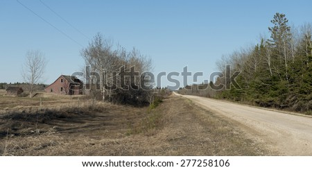 Dirt road passing through a field, Manitoba, Canada - stock photo
