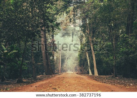 Dirt road stretching through Cambodian jungle. - stock photo
