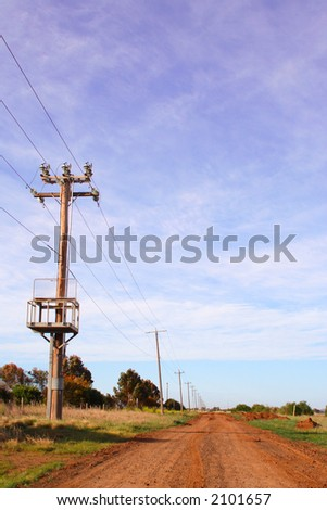 Dirt road with row of power poles
