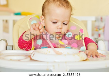 dirty baby girl is eating - stock photo