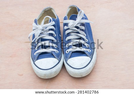 dirty blue shoes on the wood background - stock photo