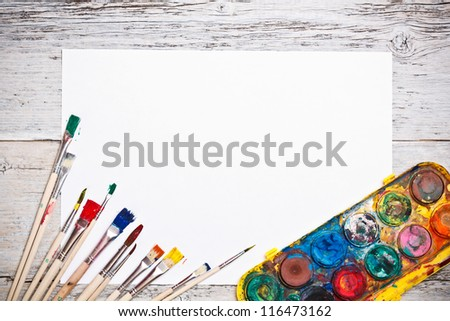 Dirty brushes with paints and paper - stock photo