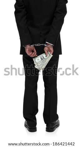 Dirty businessman in handcuffs holding money behind his back - stock photo