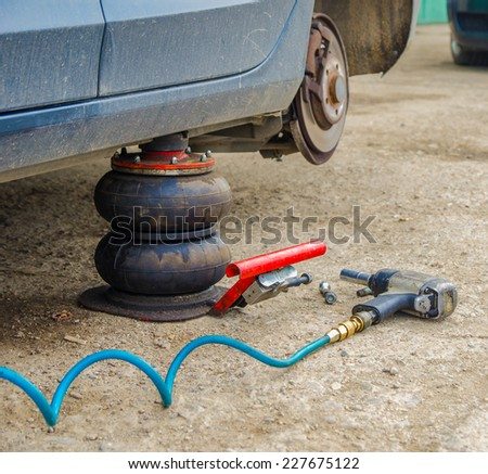 Dirty car and pneumatic tools at a service workshop for a tyre change on old concrete - stock photo