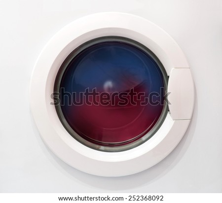 Dirty clothing being washed in washing machine - stock photo