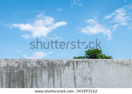 Dirty concrete wall with beautiful blue sky at the midday background - stock photo