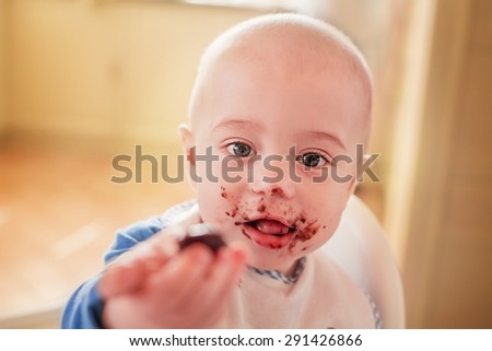 Dirty cute little boy in bib eating chocolate. Image with selective focus - stock photo